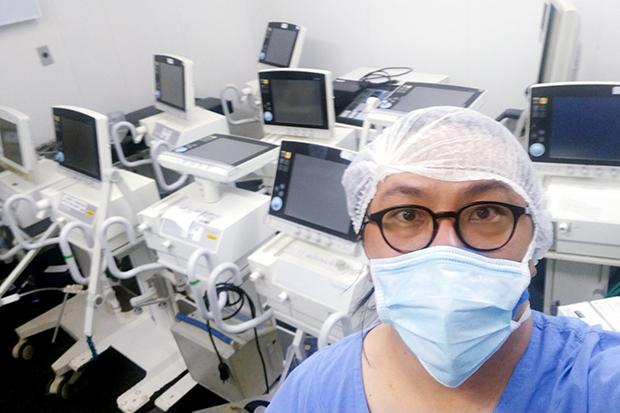 Ao lado de um microscópio, pesquisadora paramentada com luvas, óculos, máscara, jaleco e touca registra dados em um computador